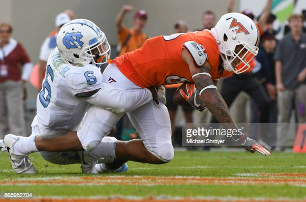 Wide receiver Eric Kumah of the Virginia Tech Hokies scores a touchdown while being defended by cornerback MJ Stewart of the North Carolina Tar Heels...
