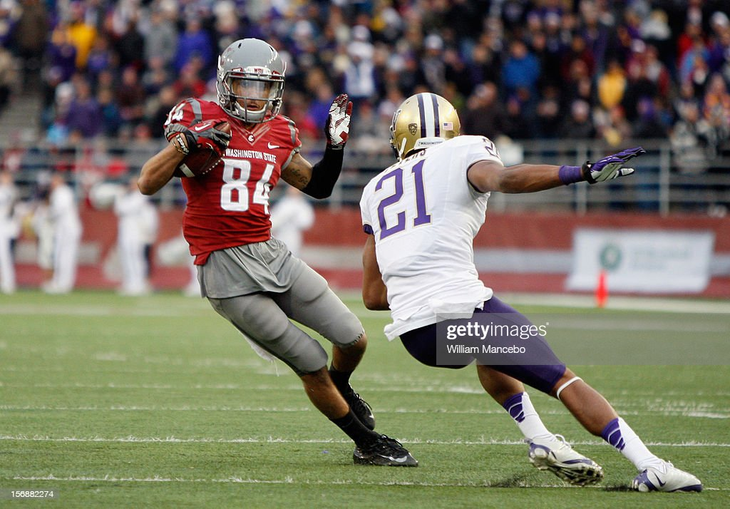 Wide receiver Gabe Marks #84 of the Washington State Cougars carries the ball against cornerback Marcus Peters #21 of the Washington Huskies at Martin Stadium on November 23, 2012 in Pullman, Washington.