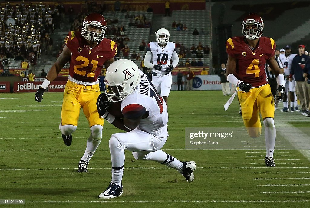 Wide receiver Garic Wharton #16 of the Arizona Wildcats goes into the end zone with a 28 yard touchdown pass in the fourth quarter to pull within a touchdown against the USC Trojans at Los Angeles Coliseum on October 10, 2013 in Los Angeles, California. USC won 38-31.