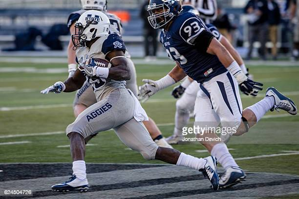 Wide receiver Gerold Bright of the Utah State Aggies runs the ball past the Nevada Wold Pack defense at Mackay Stadium on November 19 2016 in Reno...