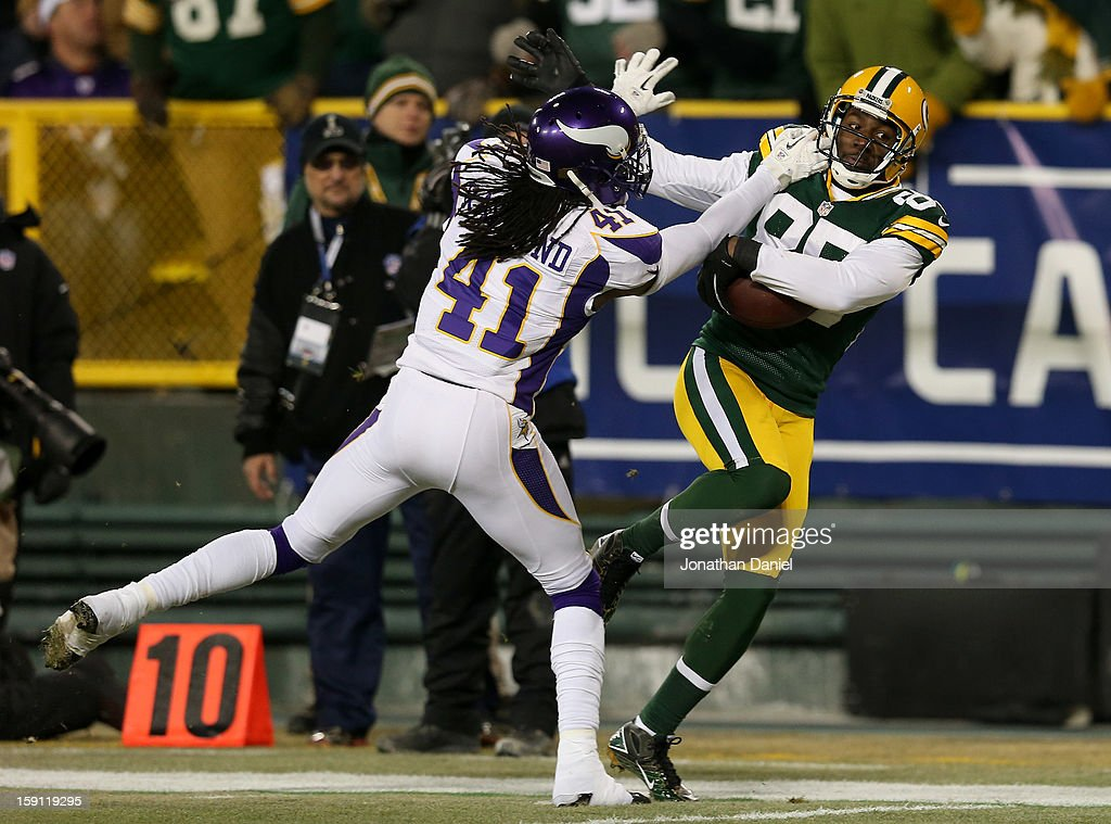 Wide receiver Greg Jennings #85 of the Green Bay Packers is pushed out of bounds by strong safety Mistral Raymond #41 of the Minnesota Vikings after a catch during the NFC Wild Card Playoff game at Lambeau Field on January 5, 2013 in Green Bay, Wisconsin.