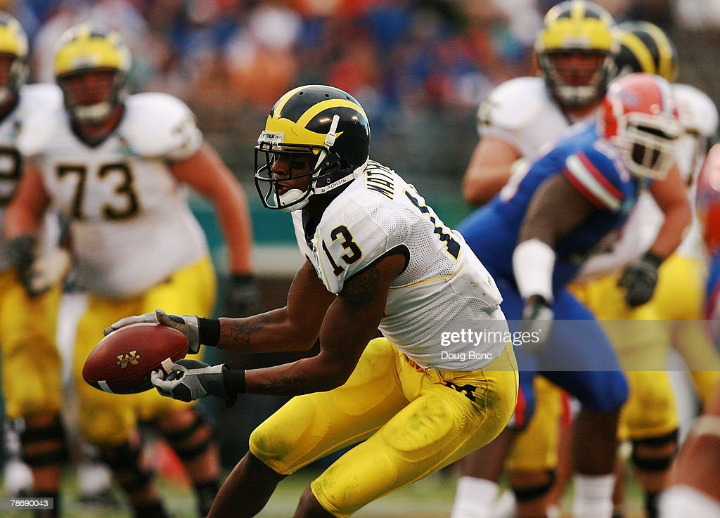 Wide receiver Greg Mathews of the Michigan Wolverines makes a catch against the Florida Gators in the Capital One Bowl at Florida Citrus Bowl on...