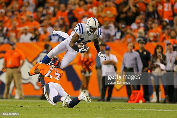 Wide receiver Hakeem Nicks of the Indianapolis Colts leaps over and is tackled by strong safety TJ Ward of the Denver Broncos during a game at Sports...
