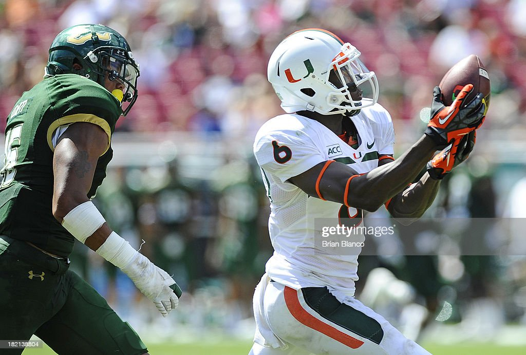 Wide receiver Herb Waters #6 of the Miami Hurricanes hauls in a pass in front of linebacker Reshard Cliett #16 of the South Florida Bulls during the third quarter on September 28, 2013 at Raymond James Stadium in Tampa, Florida.