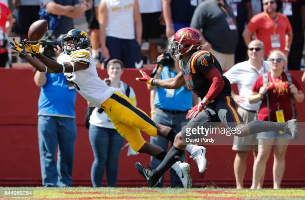Wide receiver Ihmir SmithMarsette of the Iowa Hawkeyes pulls in a touchdown pass as defensive back Evrett Edwards of the Iowa State Cyclones defends...