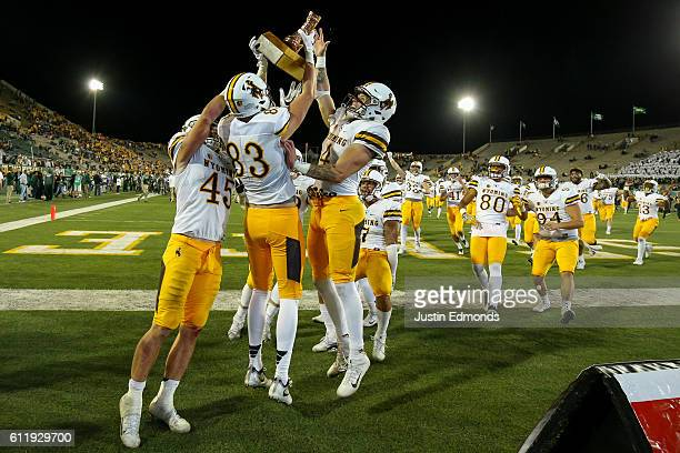 Wide receiver Jake Maulhardt of the Wyoming Cowboys hoists The Bronze Boot and celebrates with his teammates after defeating Colorado State Rams 3817...