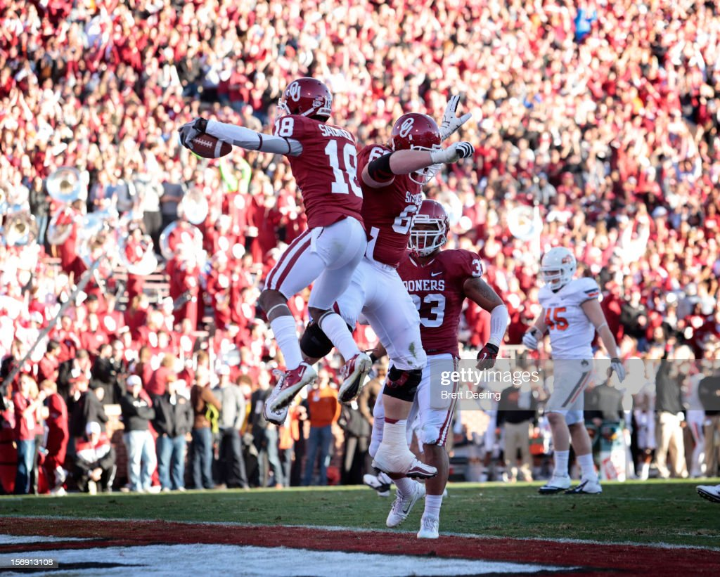 Wide receiver Jalen Saunders #18 and offensive lineman Bronson Irwin celebrate a touchdown against the Oklahoma State Cowboys November 24, 2012 at Gaylord Family-Oklahoma Memorial Stadium in Norman, Oklahoma. Oklahoma defeated Oklahoma State 51-48 in overtime.