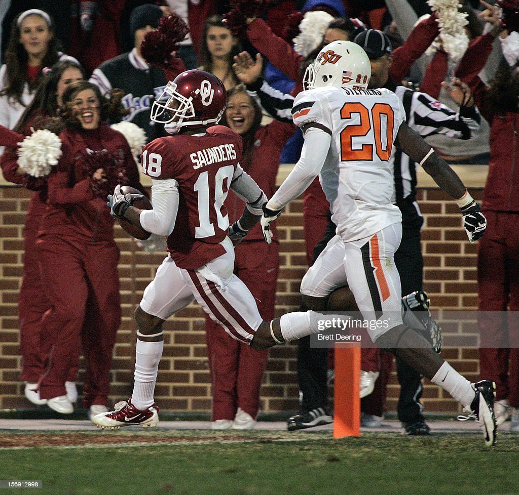Wide receiver Jalen Saunders #18 of the Oklahoma Sooners scores on an 81-yard punt return against the Oklahoma State Cowboys November 24, 2012 at Gaylord Family-Oklahoma Memorial Stadium in Norman, Oklahoma. Oklahoma defeated Oklahoma State 51-48 in overtime.