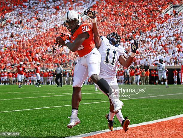 Wide receiver James Washington of the Oklahoma State Cowboys makes a reception for a touchdown in front of defensive back Dane Jackson of the...