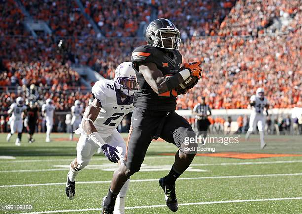 Wide receiver James Washington of the Oklahoma State Cowboys runs a reception in for a touchdown in front of cornerback Corry O'Meally of the TCU...