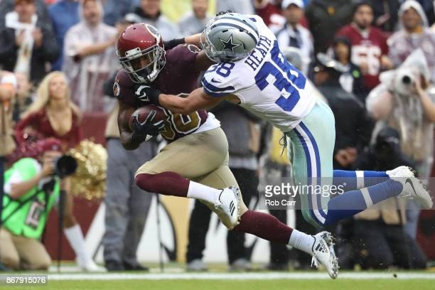 Wide receiver Jamison Crowder of the Washington Redskins stiff arms strong safety Jeff Heath of the Dallas Cowboys during the first quarter at FedEx...