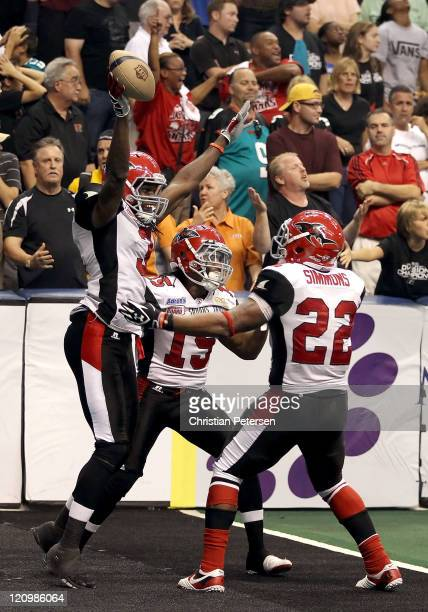 Wide receiver Jeron Harvey of the Jacksonville Sharks celebrates with Sale Key and Jamarko Simmons after scoring the game winning touchdown against...
