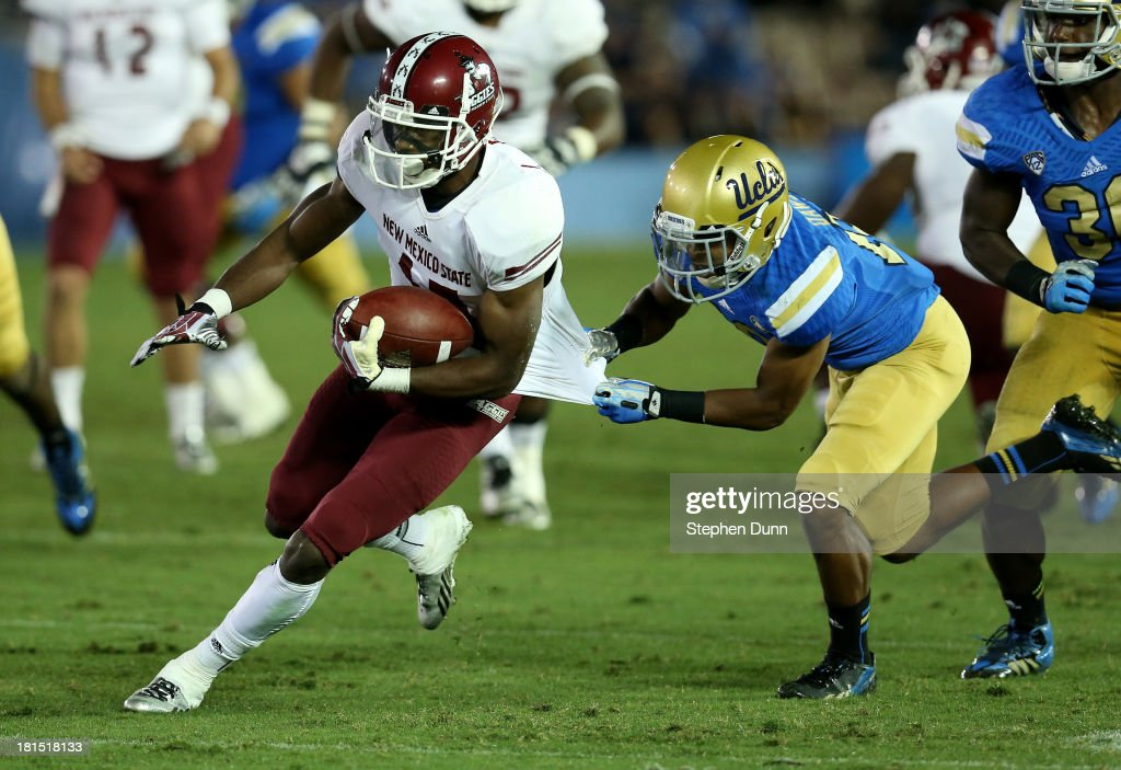 Wide receiver Jerrel Brown #17 of the New Mexico State Aggies carries the ball as cornerback Charles Dawson #18 of the UCLA Bruins pulls his jersey at the Rose Bowl on September 21, 2013 in Pasadena, California. UCLA won 59-13.