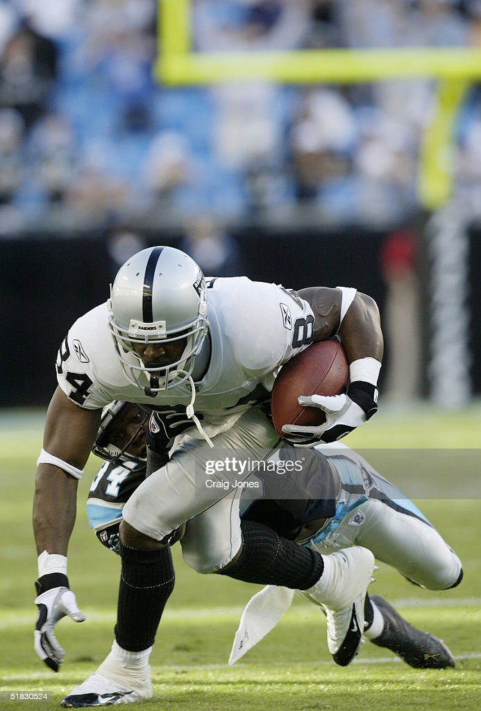 Wide receiver Jerry Porter #84 of the Oakland Raiders is tackled by cornerback Eddie Jackson #34 of the Carolina Panthers during the game at Bank of America Stadium on November 7, 2004 in Charlotte, North Carolina.