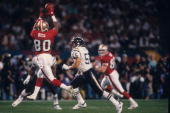 Wide receiver Jerry Rice of the San Francisco 49ers catches a pass behind linebacker Junior Seau of the San Diego Chargers in Super Bowl XXIX at Joe...
