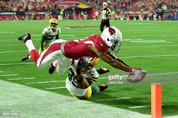 Wide receiver John Brown of the Arizona Cardinals dives for the pylon while being hit by defensive end Datone Jones of the Green Bay Packers during...