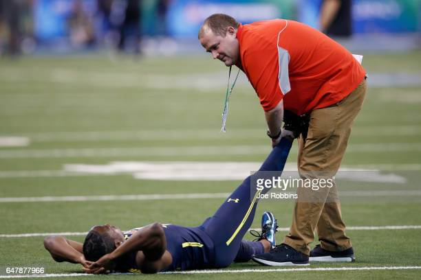 Wide receiver John Ross of Washington is looked at by a trainer after running an unofficial record 40yard dash in 422 seconds during day four of the...