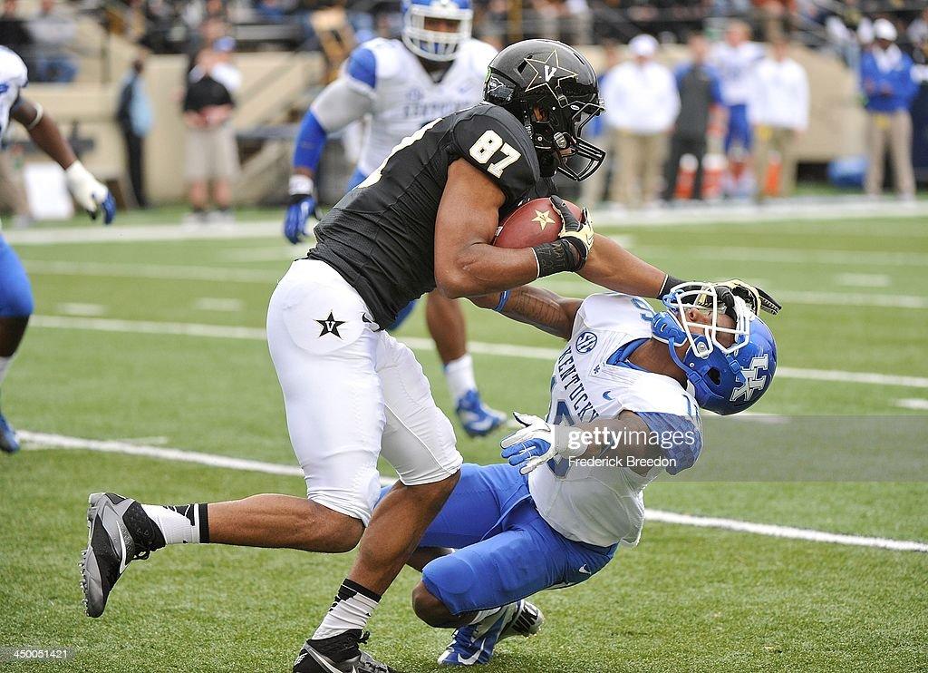 Wide receiver Jordan Matthews #87 of the Vanderbilt Commodores stiff arms Cody Quinn #16 of the Kentucky Wildcats to the ground at Vanderbilt Stadium on November 16, 2013 in Nashville, Tennessee.