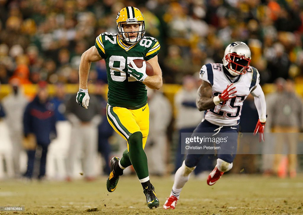 Wide receiver Jordy Nelson of the Green Bay Packers runs with the football past cornerback Kyle Arrington of the New England Patriots en route to...