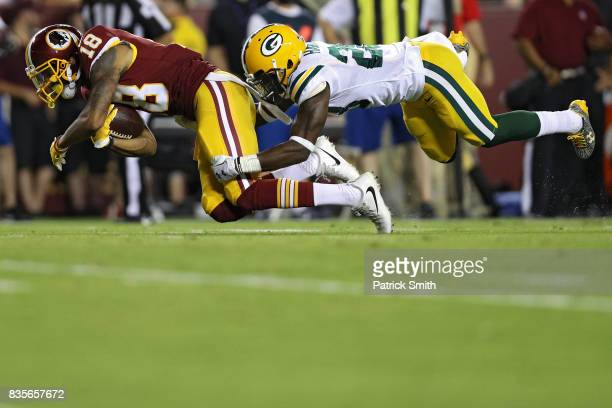 Wide receiver Josh Doctson of the Washington Redskins is tackled by cornerback Josh Hawkins of the Green Bay Packers in the first half during a...