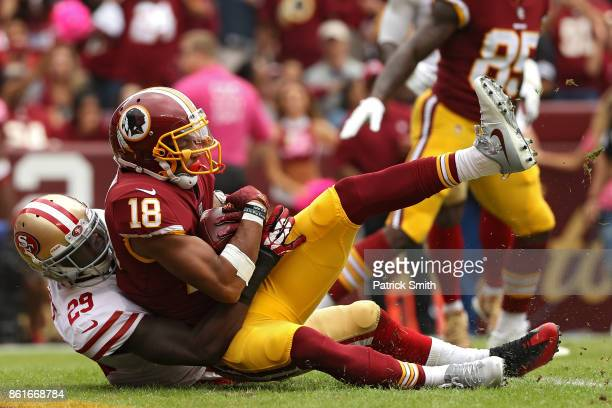 Wide receiver Josh Doctson of the Washington Redskins scores a touchdown as he is tackled by free safety Jaquiski Tartt of the San Francisco 49ers...