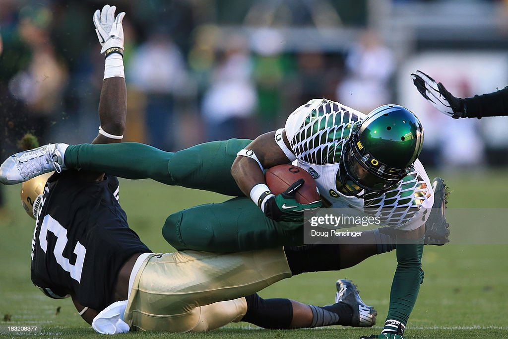 Wide receiver Josh Huff #1 of the Oregon Ducks makes a pass reception and is tackled by defensive back Kenneth Crawley #2 of the Colorado Buffaloes at Folsom Field on October 5, 2013 in Boulder, Colorado. The Ducks defeated the Buffs 57-16.