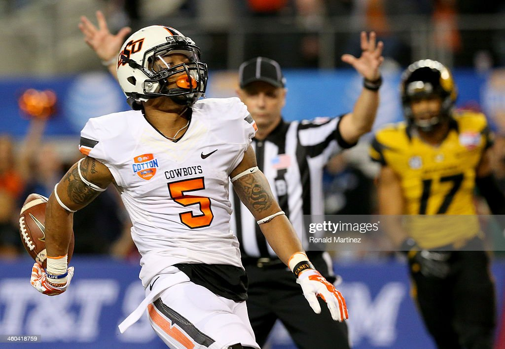Wide receiver Josh Stewart #5 of the Oklahoma State Cowboys scores a touchdown on a 40-yard catch in the first half while taking on the Missouri Tigers during the AT&T Cotton Bowl on January 3, 2014 in Arlington, Texas.