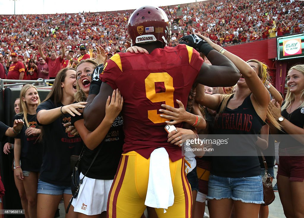 Wide receiver JuJu Smith-Schuster #9 of the USC Trojans is mobbed by a group of students behind the end zone after scoring on a 50 yard touchdown pass play in tthe first quarter against the Idaho Vandals at Los Angeles Memorial Coliseum on September 12, 2015 in Los Angeles, California.