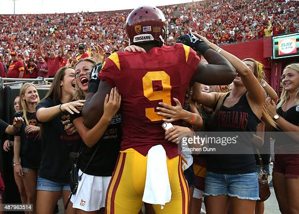 Wide receiver JuJu SmithSchuster of the USC Trojans is mobbed by a group of students behind the end zone after scoring on a 50 yard touchdown pass...