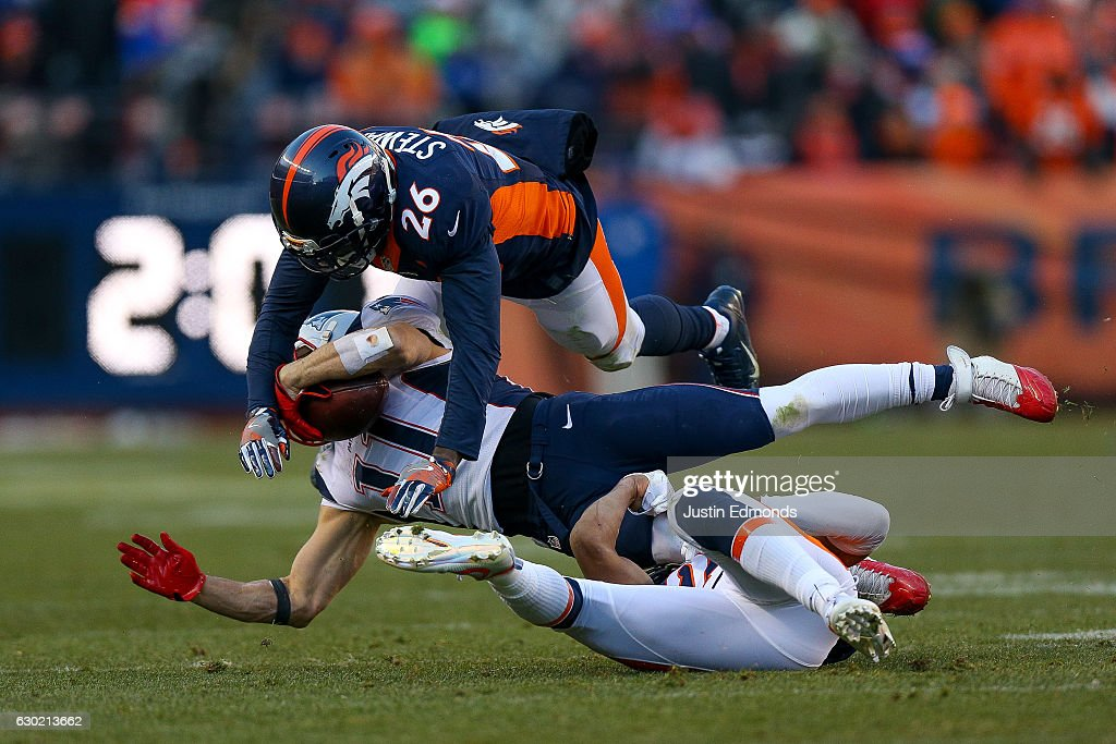 Wide receiver Julian Edelman #11 of the New England Patriots has a reception for a first down and is hit by free safety Darian Stewart #26 and strong safety T.J. Ward #43 of the Denver Broncos at Sports Authority Field at Mile High on December 18, 2016 in Denver, Colorado.