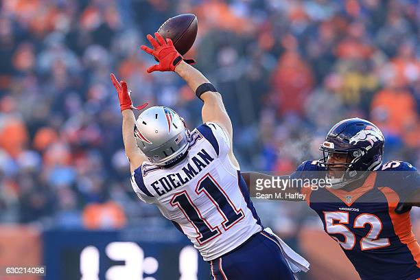 Wide receiver Julian Edelman of the New England Patriots jumps for a reception under coverage by inside linebacker Corey Nelson of the Denver Broncos...