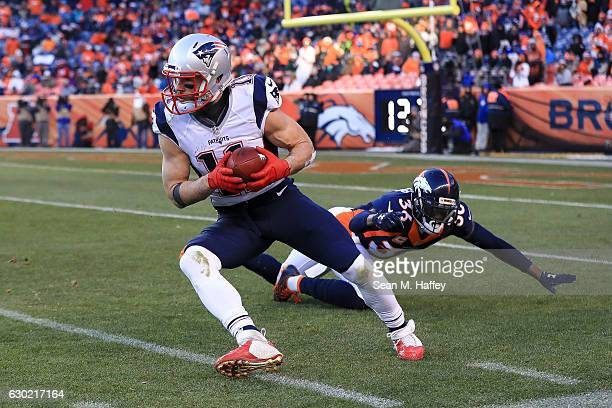 Wide receiver Julian Edelman of the New England Patriots receives a punt under coverage by cornerback Kayvon Webster of the Denver Broncos in the...