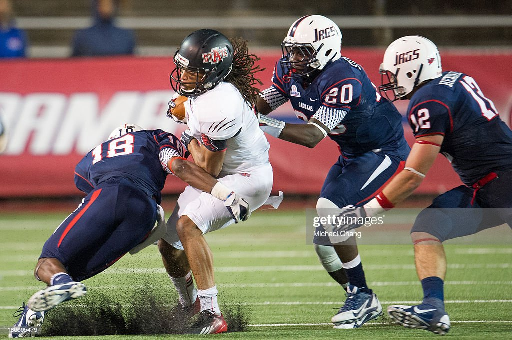 Wide receiver Julian Jones #7 of the Arkansas State Red Wolves attempts to maneuver by safety Terrell Brigham #18 of the South Alabama Jaguars on November 2, 2013 at Ladd-Peebles Stadium in Mobile, Alabama. Arkansas State defeated South Alabama 17-16.