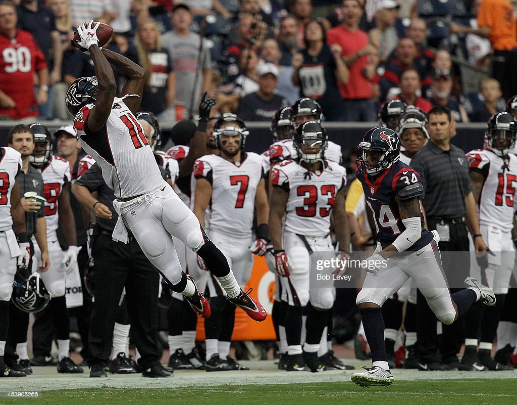 Wide receiver Julio Jones #11 of the Atlanta Falcons makes a catch as he gets behind cornerback A.J. Bouye #34 of the Houston Texans at Reliant Stadium on August 16, 2014 in Houston, Texas.