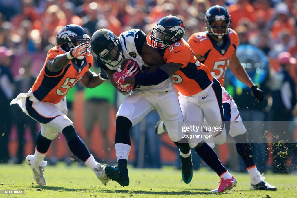 Wide receiver <a gi-track='captionPersonalityLinkClicked' href=/galleries/search?phrase=Justin+Blackmon&family=editorial&specificpeople=6236641 ng-click='$event.stopPropagation()'>Justin Blackmon</a> #14 of the Jacksonville Jaguars makes a first down reception and is tackled by cornerback <a gi-track='captionPersonalityLinkClicked' href=/galleries/search?phrase=Kayvon+Webster&family=editorial&specificpeople=6315925 ng-click='$event.stopPropagation()'>Kayvon Webster</a> #36 of the Denver Broncos and outside linebacker <a gi-track='captionPersonalityLinkClicked' href=/galleries/search?phrase=Danny+Trevathan&family=editorial&specificpeople=6475347 ng-click='$event.stopPropagation()'>Danny Trevathan</a> #59 of the Denver Broncos at Sports Authority Field at Mile High on October 13, 2013 in Denver, Colorado.