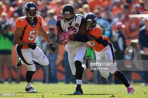 Wide receiver Justin Blackmon of the Jacksonville Jaguars makes a pass reception as cornerback Kayvon Webster of the Denver Broncos makes the tackle...
