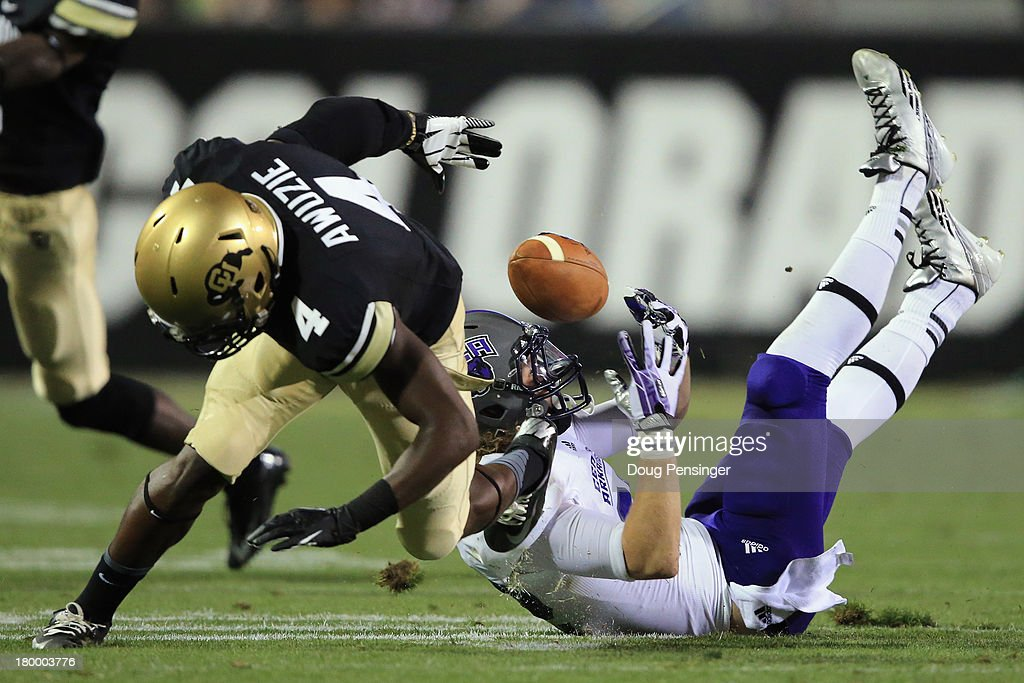 Wide receiver Justin Burdette #82 of the Central Arkansas Bears manages to make a pass reception against the defense of defensive back Chidobe Awuzie #4 of the Colorado Buffaloes at Folsom Field on September 7, 2013 in Boulder, Colorado. The Buffaloes defeated the Bears 38-24.