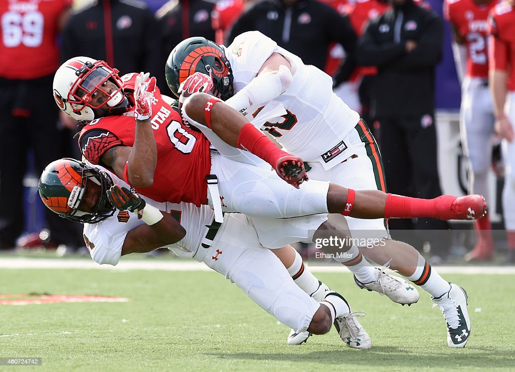 Wide receiver Kaelin Clay of the Utah Utes is tackled by defensive back DeAndre Elliott and linebacker Max Morgan of the Colorado State Rams during...