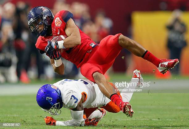 Wide receiver Kaelin DeBoskie of the Arizona Wildcats is tackled by cornerback Cleshawn Page of the Boise State Broncos after a reception during the...