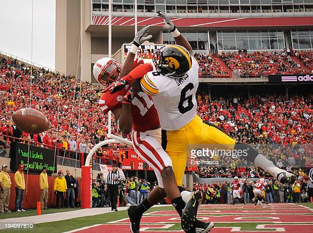 Wide receiver Keenan Davis of the Iowa Hawkeyes and cornerback Andrew Green of the Nebraska Cornhuskers fight over a ball in the end zone during...