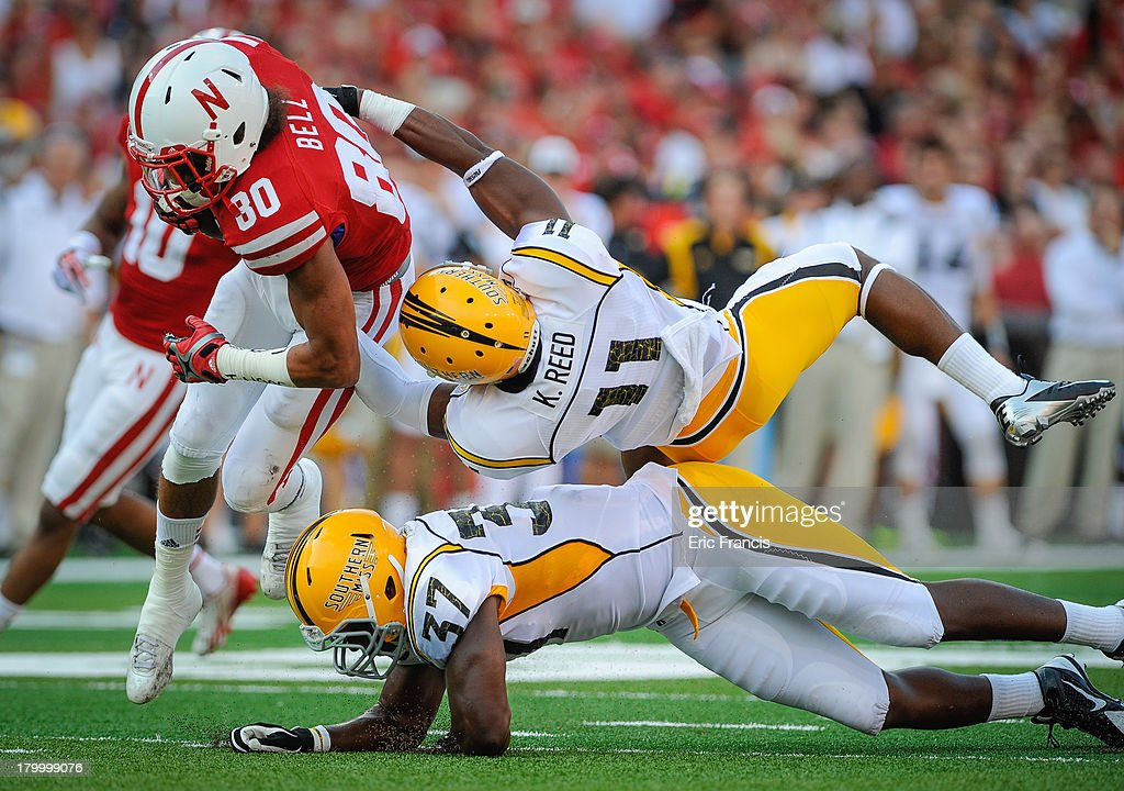 Wide receiver Kenny Bell #80 of the Nebraska Cornhuskers is tripped up by defensive back Kalan Reed #11 and linebacker Alan Howze #37 of the Southern Miss Golden Eagles during their game at Memorial Stadium on September 7, 2013 in Lincoln, Nebraska.