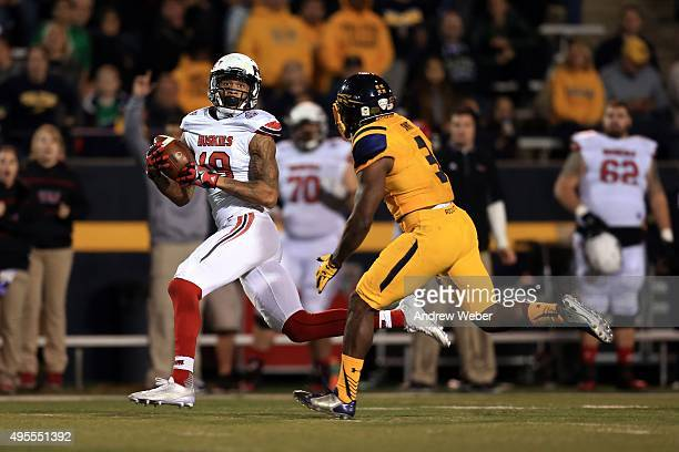 Wide receiver Kenny Golladay of the Northern Illinois Huskies catches a pass while being defended by defensive back Connery Swift of the Toledo...