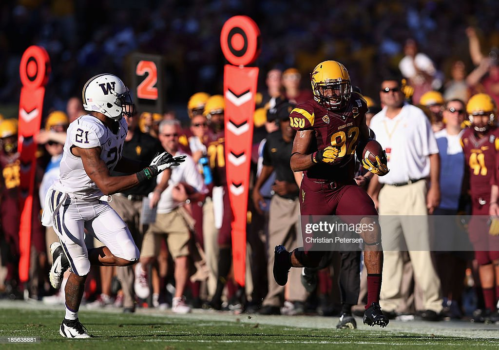 Wide receiver Kevin Ozier #82 of the Arizona State Sun Devils runs with the football past defensive back Marcus Peters #21 of the Washington Huskies during the college football game at Sun Devil Stadium on October 19, 2013 in Tempe, Arizona. The Sun Devils defeated the Huskies 53-24.