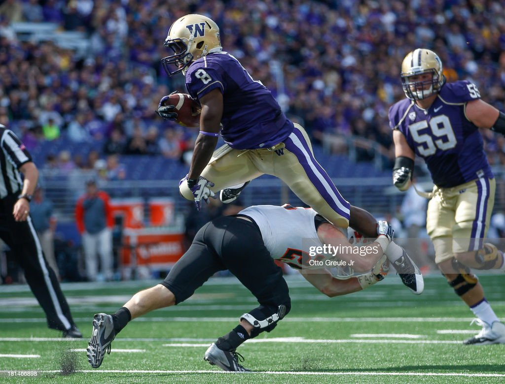 Wide receiver Kevin Smith #8 of the Washington Huskies jumps over against Tanner Davis #25 of the Idaho State Bengals on September 21, 2013 at Husky Stadium in Seattle, Washington.