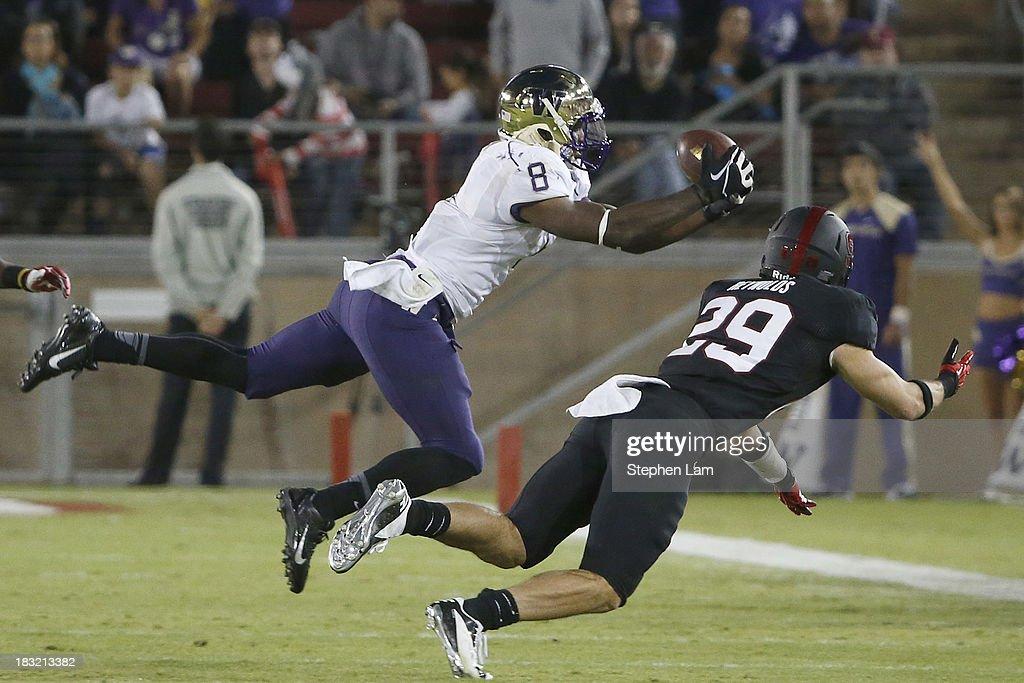 Wide receiver Kevin Smith #8 of the Washington Huskies jumps to make a 17-yard catch while safety Ed Reynolds #29 of the Stanford Cardinal defends during the fourth quarter of their game on October 5, 2013 at Stanford Stadium in Stanford, California. The Cardinal defeated the Huskies 31-28.