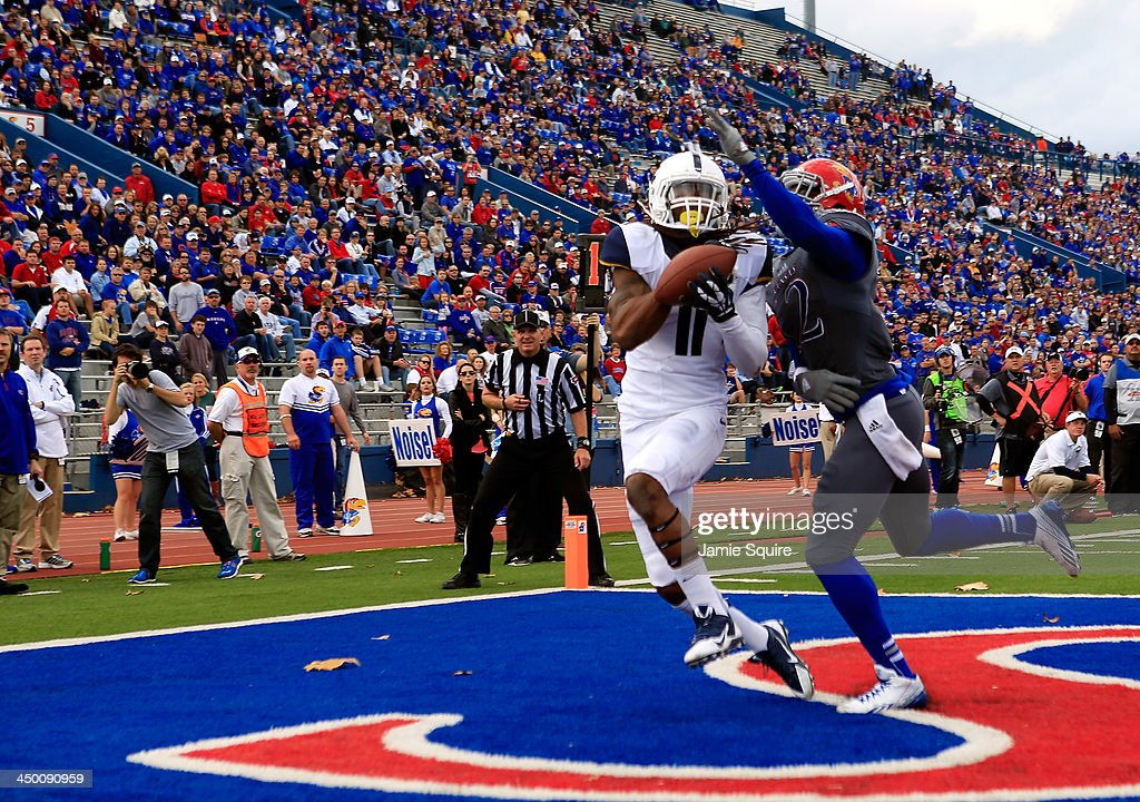 Wide receiver Kevin White #11 of the West Virginia Mountaineers cathes a pass for a touchdwon as cornerback Dexter McDonald #12 of the Kansas Jayhawks defends during the game at Memorial Stadium on November 16, 2013 in Lawrence, Kansas.