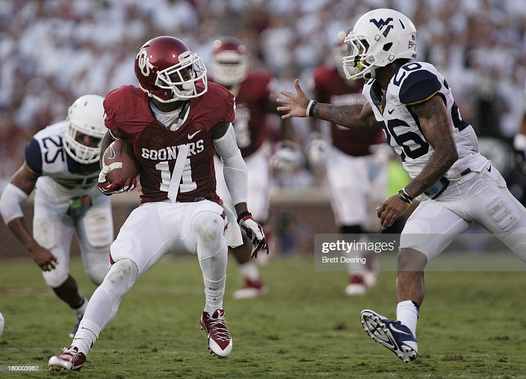 Wide receiver Lacoltan Bester #11 of the Oklahoma Sooners evades cornerback Travis Bell #26 of the West Virginia Mountaineers September 7, 2013 at Gaylord Family-Oklahoma Memorial Stadium in Norman, Oklahoma. Oklahoma defeated West Virginia 16-7.