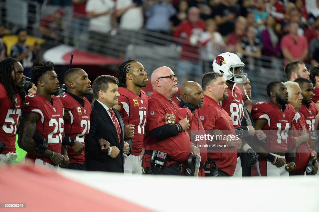 Wide receiver Larry Fitzgerald #11 and head coach Bruce Arians of the Arizona Cardinals link arms during the National Anthem before the start of the NFL game against the Dallas Cowboys at the University of Phoenix Stadium on September 25, 2017 in Glendale, Arizona.