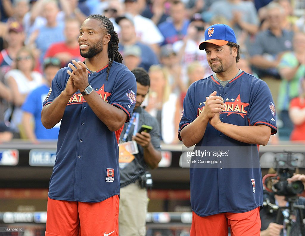 Wide receiver Larry Fitzgerald of the Arizona Cardinals (L) and former Major League Baseball player Mike Piazza stand together prior to the 2014 Taco Bell MLB All-Star Legends & Celebrity Softball Game at Target Field on July 13, 2014 in Minneapolis, Minnesota.