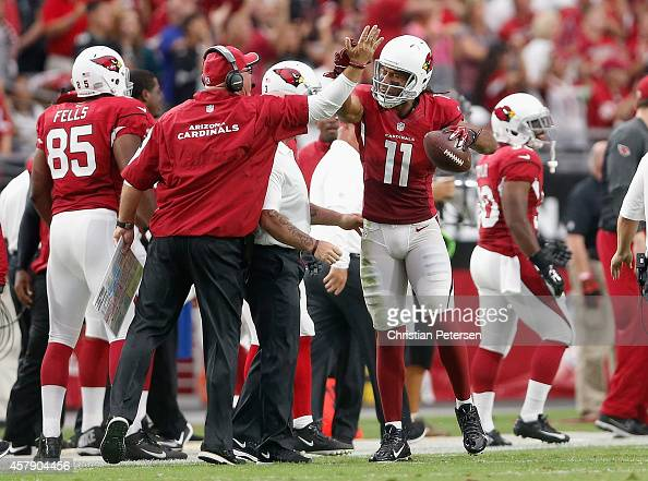 Wide receiver Larry Fitzgerald of the Arizona Cardinals celebrates with head coach Bruce Arians after scoring on an 80yard touchdown reception...